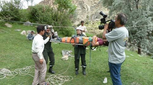 Faridoun Hemani films a reluctant cameraman Usman \'Hero\' Saleem, as he is put on a stretcher to be sent across the gorge at Hoper, in order to film a POV shot